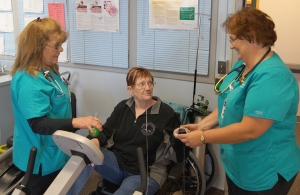 woman in pulmonary rehab with two nurses